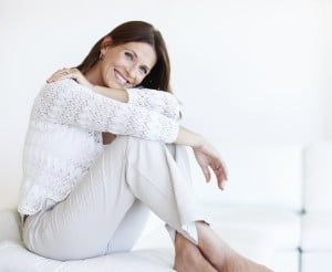 Portrait of relaxed woman sitting on couch with smile