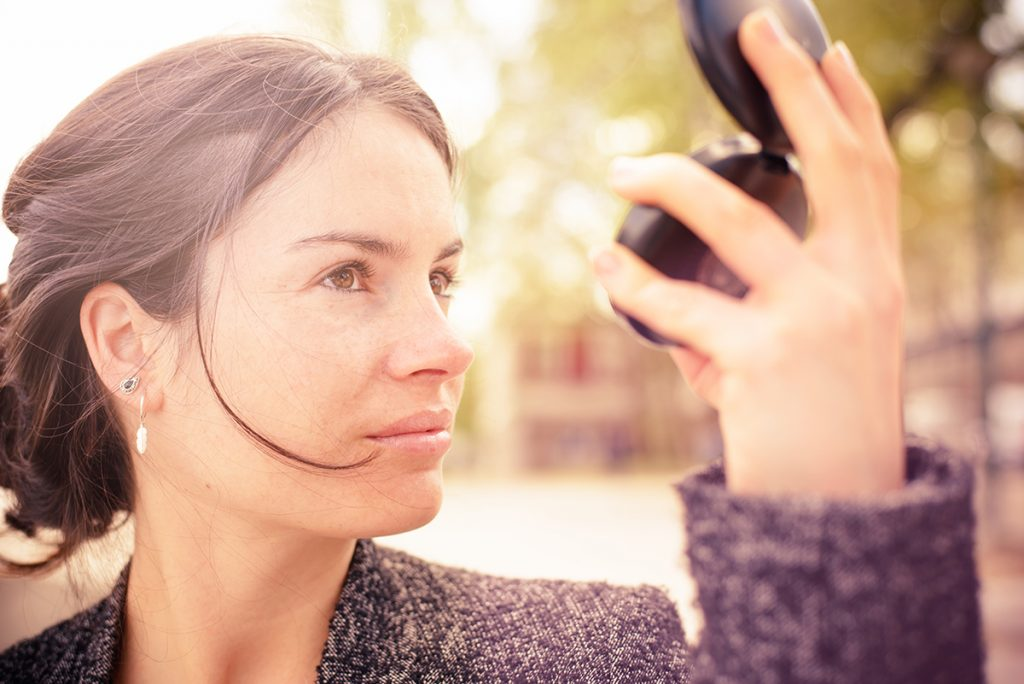 Woman check complexion in a compact mirror