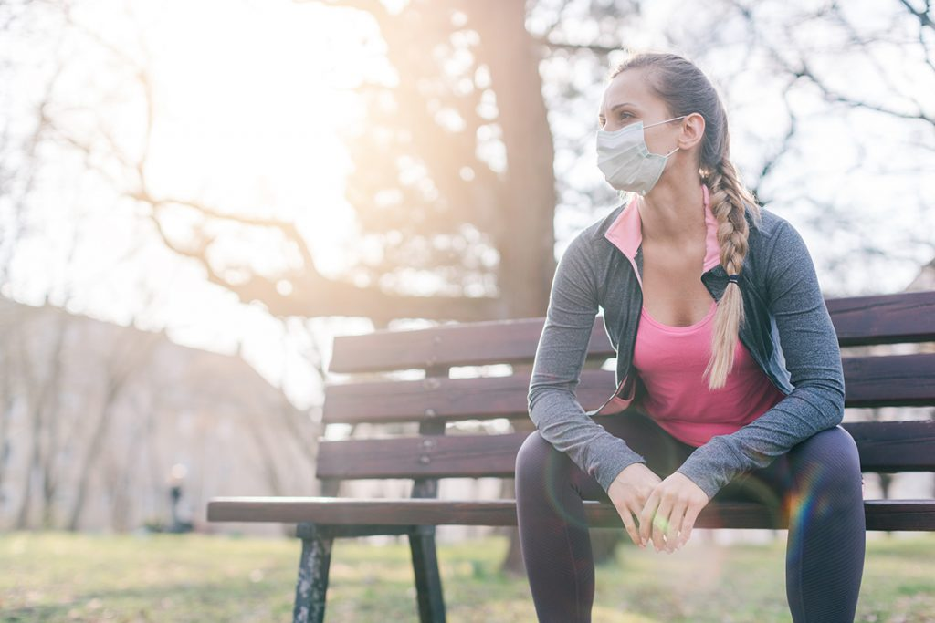 Young woman working out with mask on
