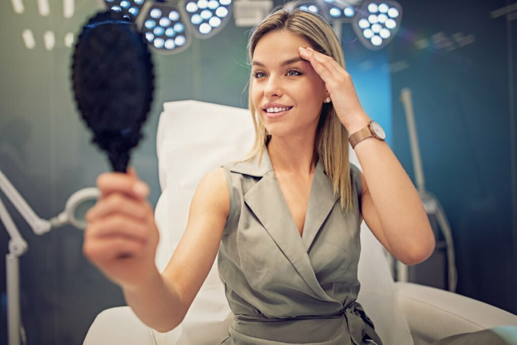 Young Woman Looks in Mirror After Preventative Anti-Aging BOTOX with Dr. Movassaghi and Karen at Ziba Medical Spa